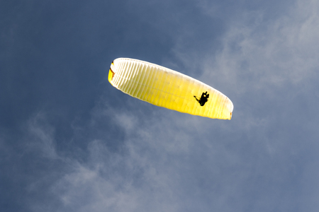 Paragliding in the blue sky with clouds
