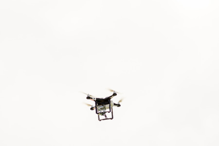 Black drone flying and filming in the sky Stock Photo