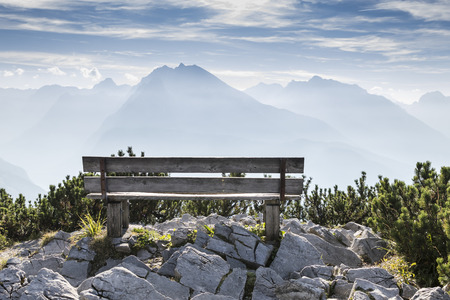 Empty park bench in high mountains, view from Eagles nest in the bavarian Alps near Berchtesgaden in Germany Stock Photo