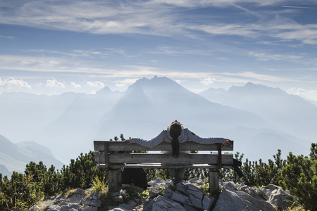 woman sitting on bench in mountains, view from Eagles nest in the bavarian Alps near Berchtesgaden in Germany