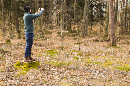 bearded man taking photo with smartphone in the forest