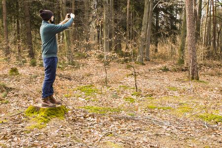 Bärtiger Mann , der Foto mit Smartphone im Wald macht