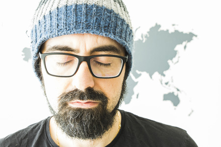 Young bearded man on white background with world map