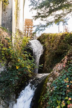 old wooden water mill on stone wall Standard-Bild