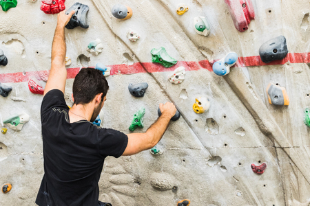 A Man practicing rock climbing on artificial wall indoors. Active lifestyle and bouldering concept.