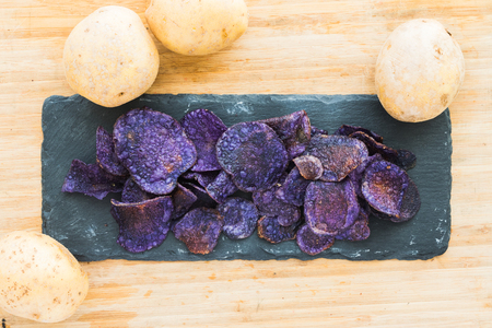 A Heap of purple potato chips on wooden background