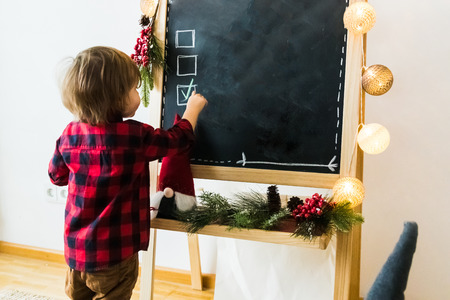 boy checking options on a blackboard with copyspace