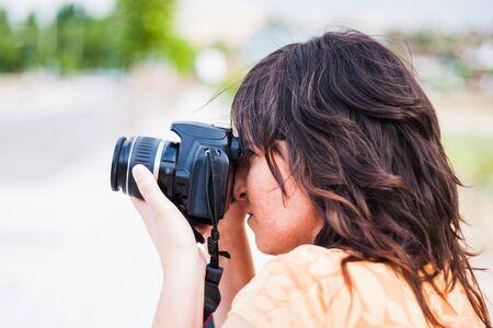 Una giovane ragazza che fotografa con la fotocamera reflex