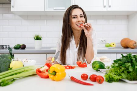 Cheerful Young Brunette Woman Tasting Bell Pepper