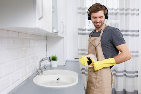 Young Man Enjoys Music While Washing Dishes