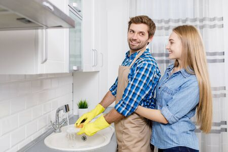 Girl Hugging Her Spouse as He Washes Dishes 스톡 콘텐츠