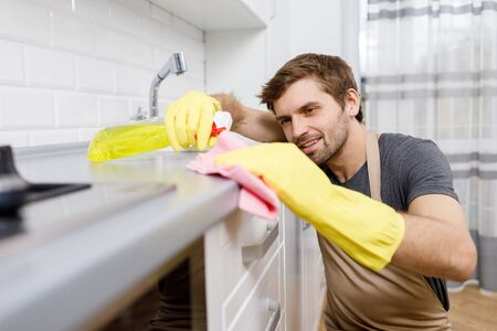 Young Man in Yellow Gloves Using Cleanser