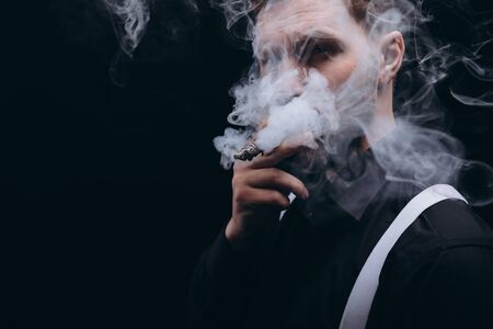 Close-up of Bearded Man Smoking a Cigar, Face Covered With Smoke Stockfoto