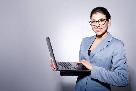Alegre, sonriente, mujer de negocios, en, anteojos, tenencia, computadora portátil Foto de archivo
