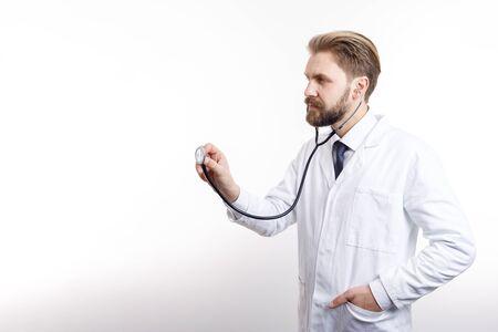 Pensativo médico medio vuelto en bata blanca auscultando