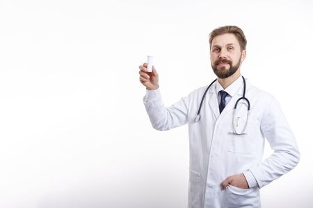 Smiling Physician With Stethoscope Demonstrating a Plastic Bottle of Medication