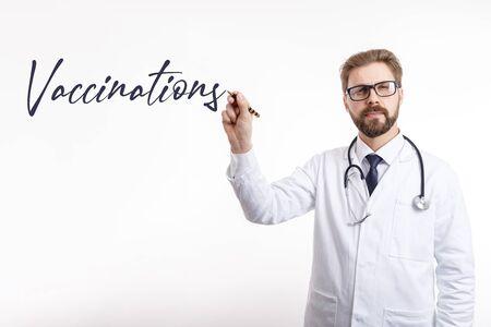 Männlicher Arzt, der das Impfwort in die Luft schreibt Standard-Bild