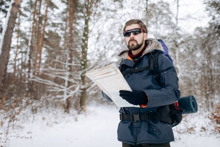 Hiker Checking Map to Orientate in Snow-clad Forest