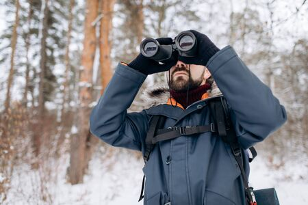 Bearded man using binoculars to orientate while his winter forest trip