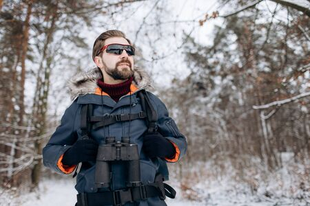 Enthusiastic Hiker in Anorak and Mirrored Glasses in Snow-clad Forest