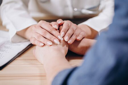 Medical Employee Covering Patients Hands With Her Own Hands