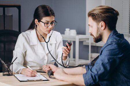 Female Medical Employee Measuring Patients Blood Pressure