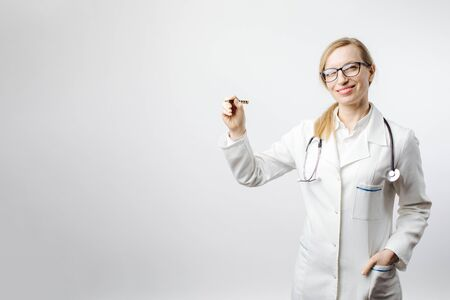 Smiling lady in medical clothing pointing on empty space Stock fotó
