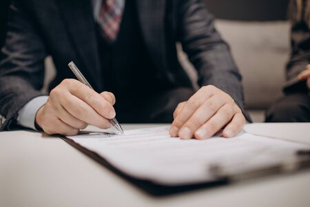 Close up of mature businessman in stylish suit sitting on couch, holding pen and signing financial agreement. Concept of people, finance and cooperation.