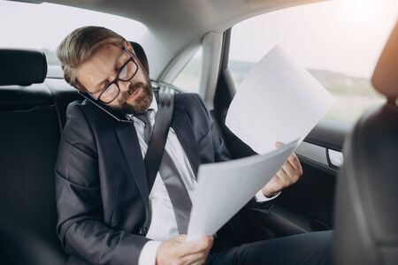 Bearded businessman in formal clothing having online consultation with private lawyer while riding car. Mature man in eyeglasses talking on smartphone and looking through new business contract. Standard-Bild