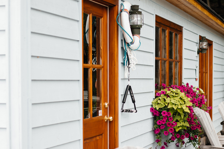 wooden front door to a home, with flowers outdoor