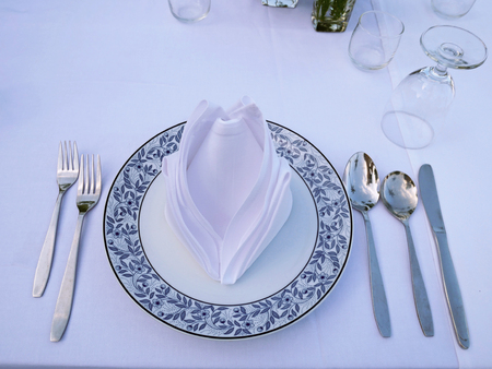 The dinner table for customer. There are spoons, folks, white napkin and grass on the white table. Imagens
