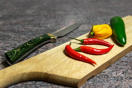 Red yellow and green hot peppers on wooden cutting board Stock Photo