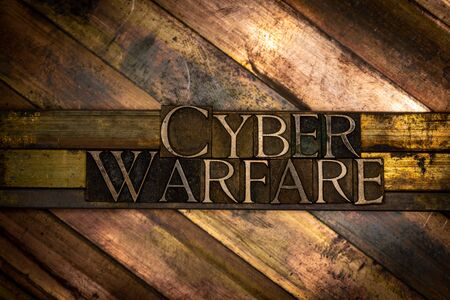 Photo of real authentic typeset letters forming Cyber Warfare text on vintage textured grunge copper background 写真素材
