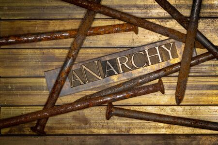 Photo of real authentic typeset letters forming Anarchy text with large rusty nails on vintage textured grunge copper and gold background 版權商用圖片