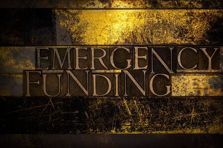 Photo of real authentic typeset letters forming Emergency Funding text on vintage textured grunge copper and gold background