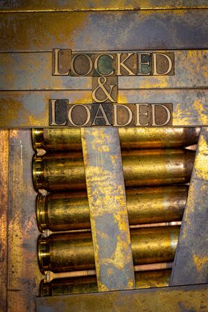 Photo of real authentic typeset letters forming Locked and Loaded text on vintage textured grunge copper and gold background with 50 cal bullet casings 版權商用圖片