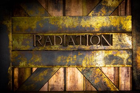 Photo of real authentic typeset letters forming Radiation text on vintage textured grunge copper background