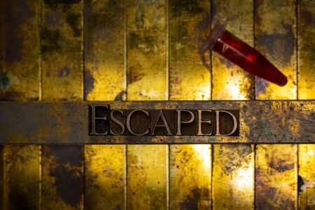 Photo of real authentic typeset letters forming Escaped text with red fluid filled laboratory vial on vintage textured grunge copper and gold background