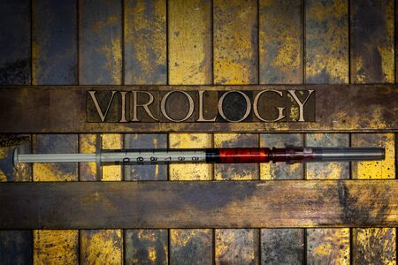 Photo of real authentic typeset letters forming Virology text with red fluid filled syringe on vintage textured grunge copper background