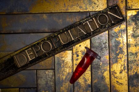 Photo of real authentic typeset letters forming Depopulation text with red fluid filled laboratory vial on vintage textured grunge copper background