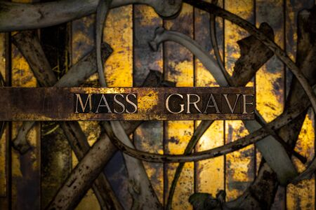 Photo of real authentic typeset letters with selective focus on Mass Grave text over skeletal bones on vintage textured grunge copper and gold background Imagens
