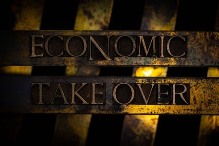 Photo of real authentic typeset letters forming Economic Take Over text on vintage textured grunge copper background