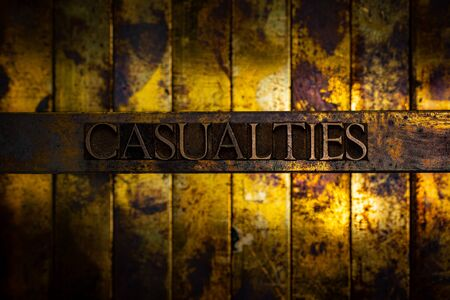 Photo of real authentic typeset letters forming Casualties text on vintage textured grunge copper background