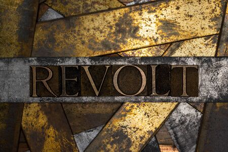 Photo of real authentic typeset letters forming Revolt text on vintage textured grunge copper and black background