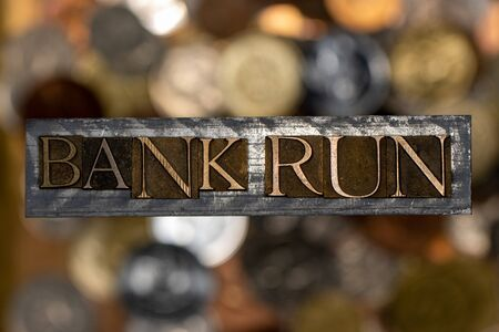 Photo of real authentic typeset letters forming Bank Run text on vintage textured silver grunge copper and gold background