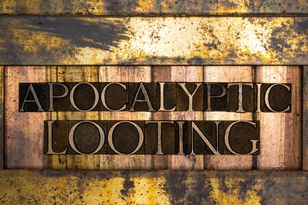 Photo of real authentic typeset letters forming Apocalyptic Looting text on vintage textured silver grunge copper and gold background