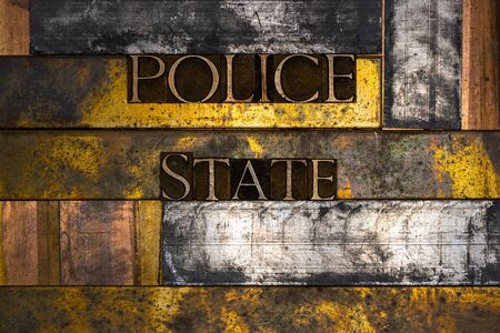 Photo of real authentic typeset letters forming Police State text on vintage textured silver grunge copper and gold background