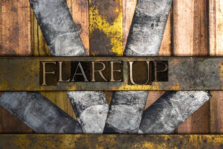Photo of real authentic typeset letters forming Flare Up text on vintage textured silver grunge copper and gold background