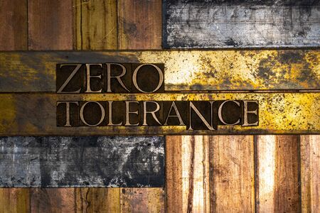 Photo of real authentic typeset letters forming Zero Tolerance text on vintage textured silver grunge copper and gold background