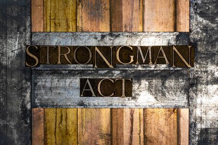 Photo of real authentic typeset letters forming Strongman Act text on vintage textured silver grunge copper and gold background